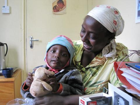 A grandmother with her grandchild - consoled by a small teddy bear.